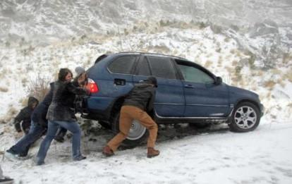 Photo of friends helping get a car unstuck.